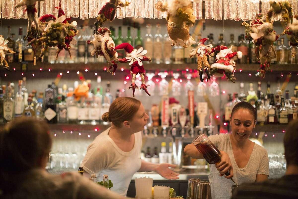 Santa dolls hang at Brass Tacks, a Hayes Valley bar, as Lindsey Baird, left, and Nehiel Nazzal, right, bar tend in San Francisco, Calif. on Thursday, December 18, 2014. The bar has a vast collection of Santa dolls from the previous tenant, the gay bar Marlena's,