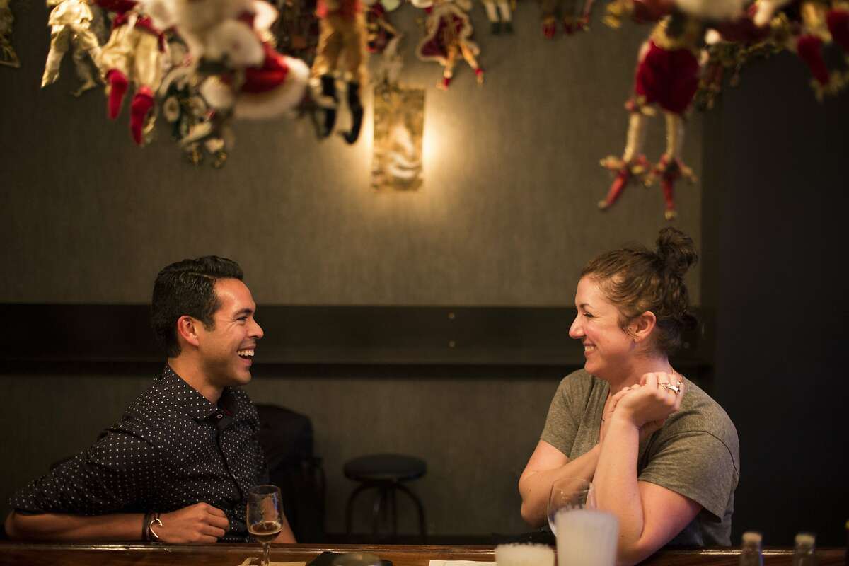 Anthony Lupian, of San Francisco, talks to Ashley Fargeon, of San Francisco, at Brass Tacks, a Hayes Valley bar, in San Francisco, Calif. on Thursday, December 18, 2014. The bar has a vast collection of Santa dolls from the previous tenant, the gay bar Marlena's.