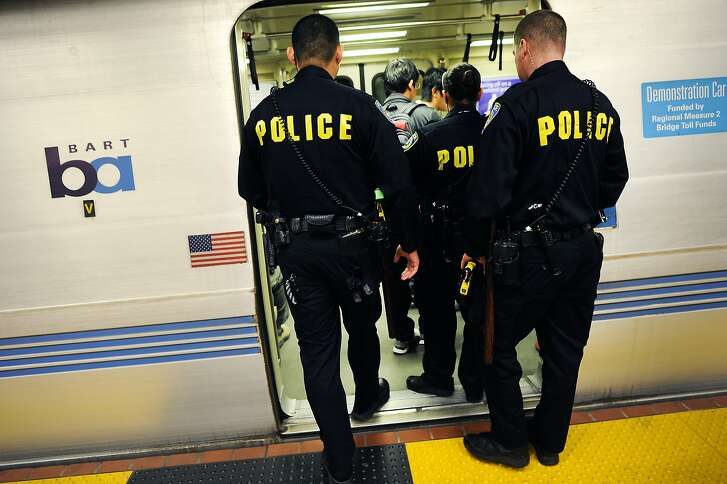 (L-R)BART Police Officers Jung,  Strickfaden  and Rudy board a train back to Powell Street station after searching for a suspect outside the 24th Street BART station in San Francisco, CA, on Thursday, December 18, 2014.