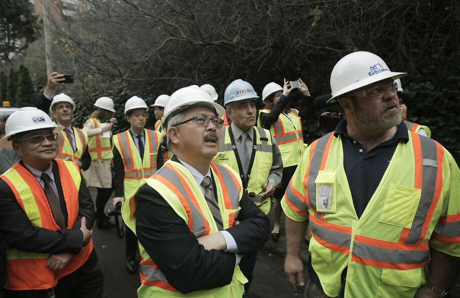 Mayor Ed Lee, (center) joins the project contractor Daniel Journeaux, (right) for an overview of the work as the San Francisco Public Works department begins the Telegraph Hill Rock Slope Improvement project to stabilize the crumbling cliff below Coit Tower in San Francisco, Calif. on Tuesday Dec. 9, 2014. Photo: Michael Macor, The Chronicle