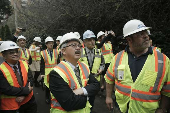 Mayor Ed Lee, (center) joins the project contractor Daniel Journeaux, (right) for an overview of the work as the San Francisco Public Works department begins the Telegraph Hill Rock Slope Improvement project to stabilize the crumbling cliff below Coit Tower in San Francisco, Calif. on Tuesday Dec. 9, 2014.