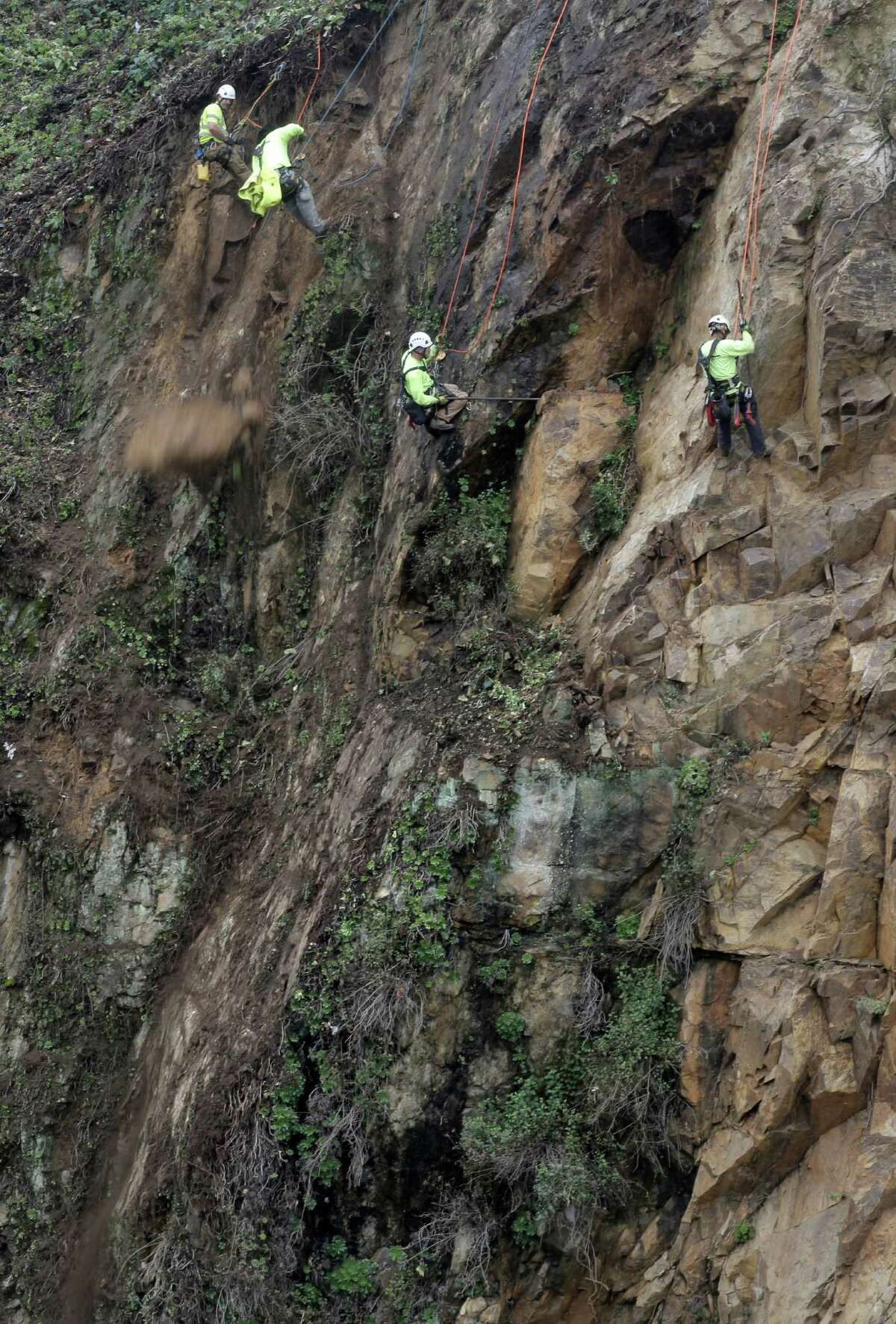 Rock remediation technicians (l to r) Jamie Steele, Adrian Coronado, John Brown and Feliciano Ramos begin the work of removing loose rock and vegetation, as the San Francisco Public Works department begins a six-month project to stabilize the crumbling cliff below Coit Tower in San Francisco, Calif. as seen on Tuesday Dec. 9, 2014.