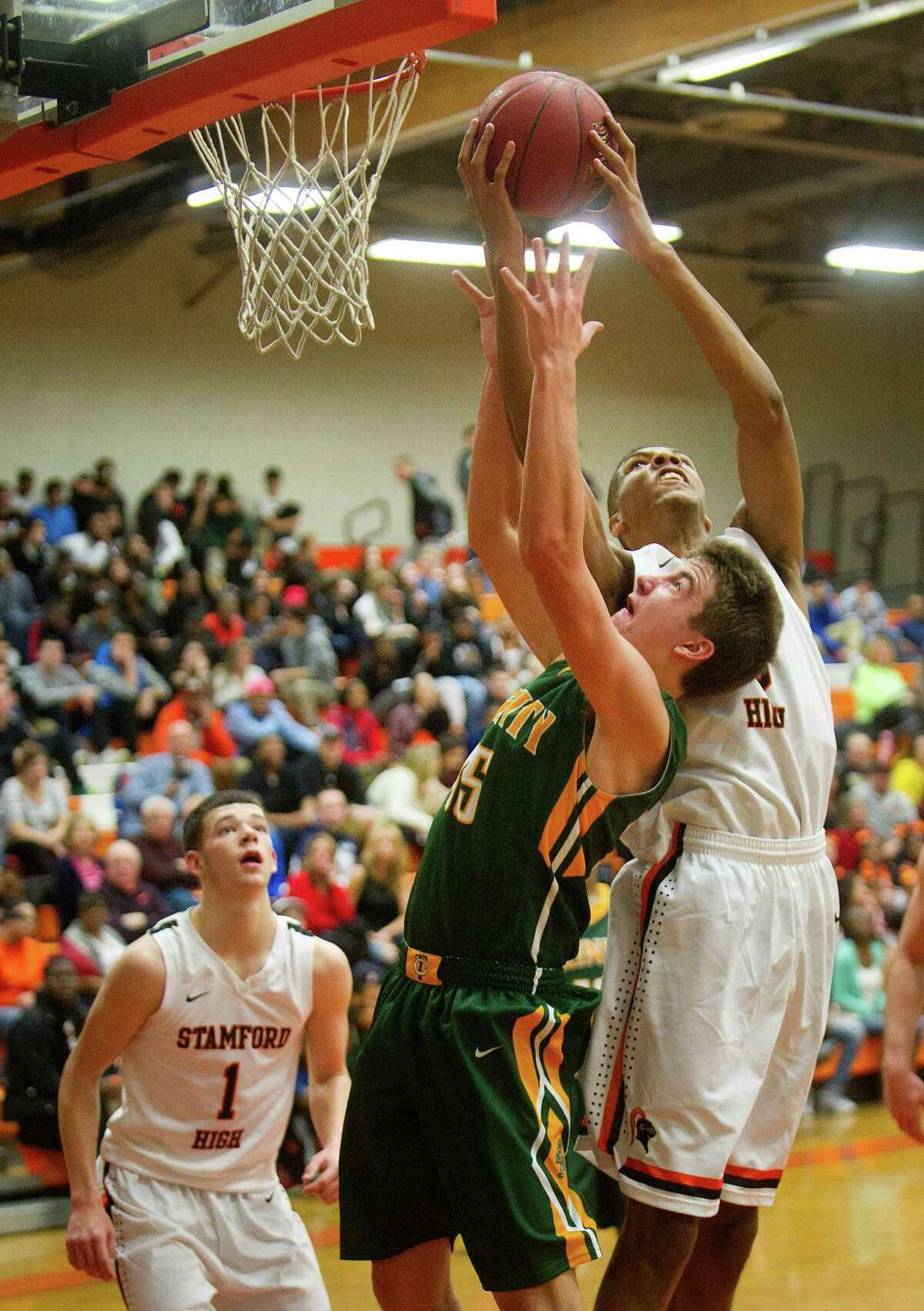 Stamford's Kweshon Askew gets the rebound as Trinity Catholic's Johnny Somers reaches for the ball during Friday's basketball game at Stamford High School on December 19, 2014.