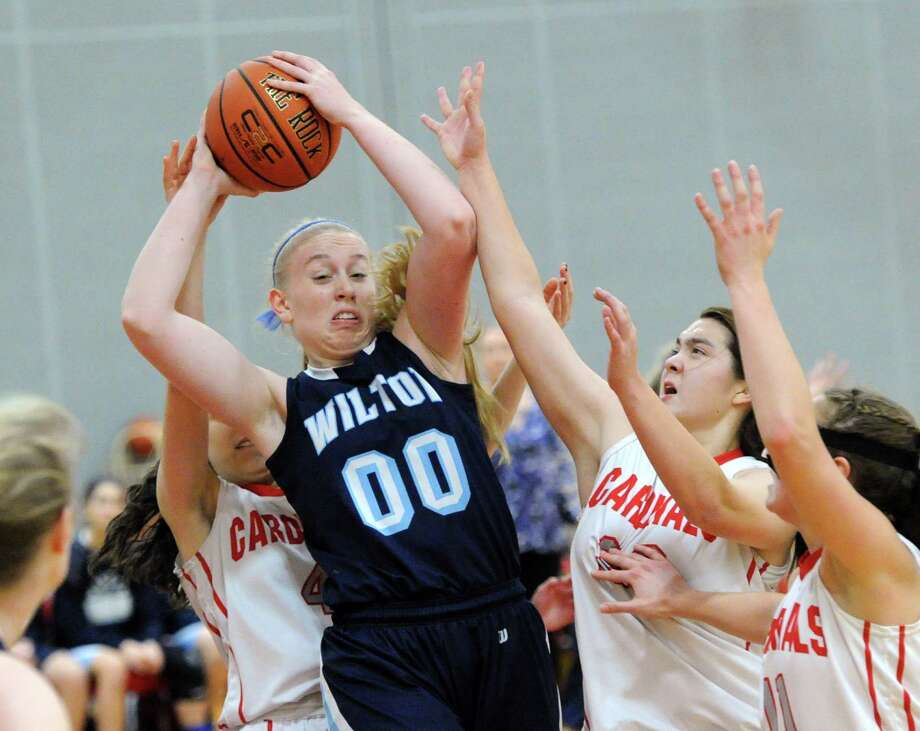 Erica Meyer (#00) of Wilton grabs a rebound over a group of Greenwich players including from left, Leigh Galletta, Jamie Kockenmeister and Alexa Moses during the girls high school basketball game between Greenwich High School and Wilton High School at Greenwich, Conn., Friday, Dec. 19, 2014. Photo: Bob Luckey / Greenwich Time