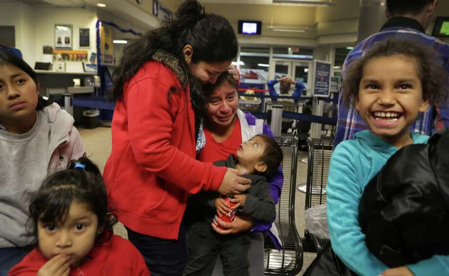 Lisvette Sanches Rodriguez of El Salvador comforts Vina Lopez of Guatemala, holding her 2-year-old son, after Central America were given food and clothing following their release from a detention facility in Karnes County. Photo: Bob Owen /San Antonio Express-News / © 2014 San Antonio Express-News