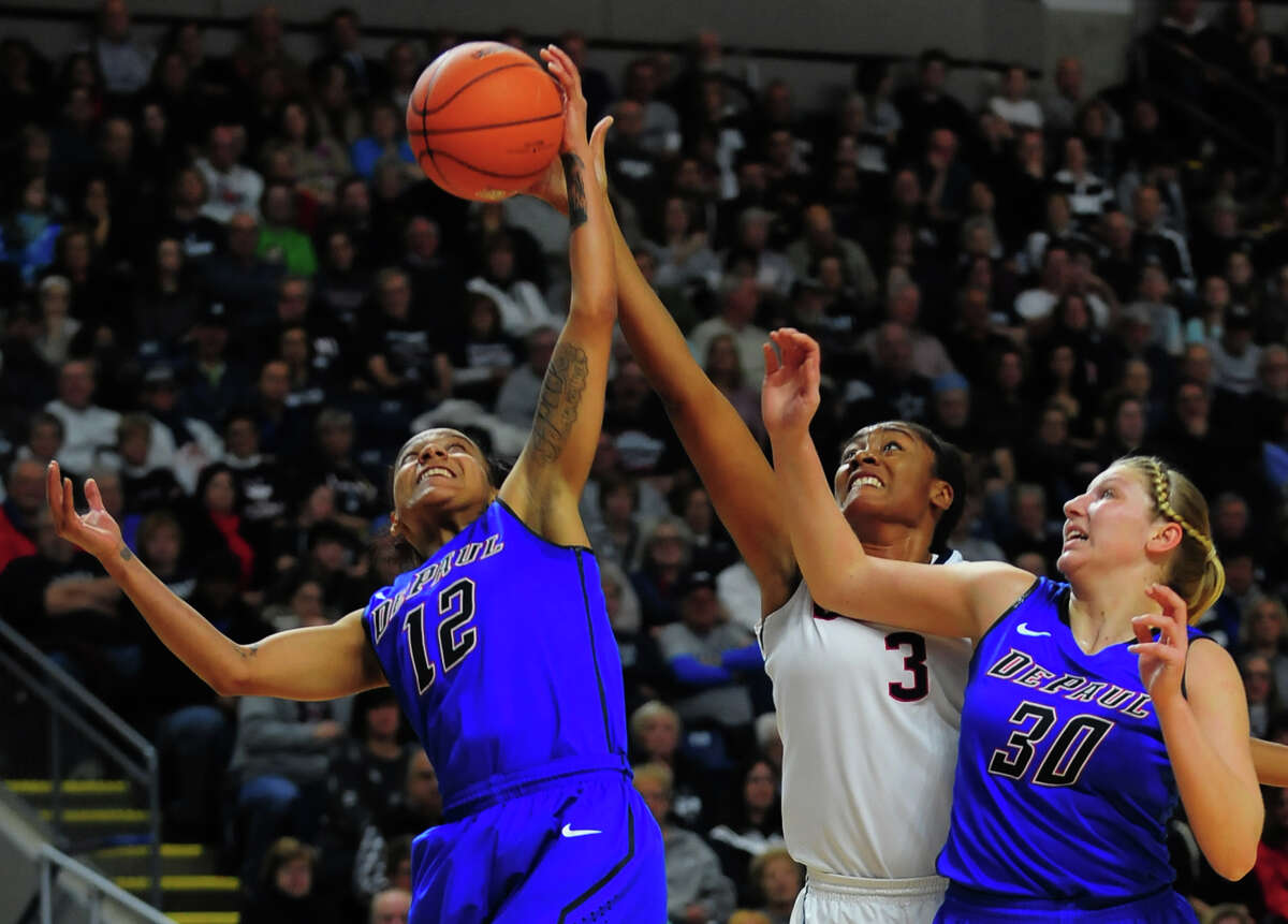 UConn's Morgan Tuck, center, and DePaul's Brittany Hrynko, left, reach for a rebound, during women's baskeball action at the Webster Bank Arena in Bridgeport on Friday Dec. 19, 2014. At right is DePaul's Megan Podkowa.