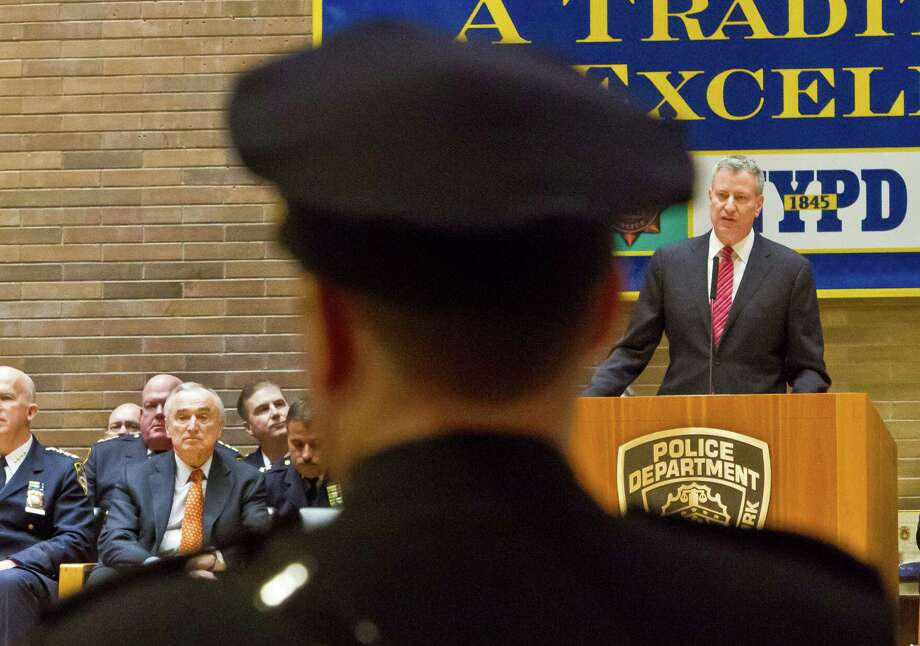 Commissioner Bill Bratton, fourth from left, sit among police officials listening as Mayor Bill de Blasio, far right, new NYPD detectives during a promotions ceremony, Friday, Dec. 19, 2014, in New York.  Even as New York's police department takes heat for its tactics in the outrage over the Eric Garner chokehold case, year-end crime statistics show two clear trends: low-level arrests are holding steady and overall crime continues to fall.  (AP Photo/Bebeto Matthews) ORG XMIT: NYBM104 Photo: Bebeto Matthews / AP