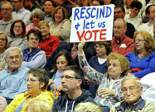East Greenbush resident Mary Murphy holds a sign while listening to a  presentation by Saratoga Casino and Raceway on a proposed Casino in East Greenbush during a meeting at Columbia High School in East Greenbush, N.Y., Monday, May 19, 2014. (Hans Pennink / Special to the Times Union) ORG XMIT: HP105 Photo: Hans Pennink / Hans Pennink