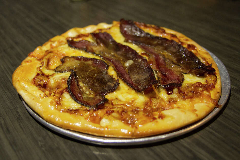 BBQ brisket pizza with BBQ sauce, mozzarella cheese and sliced brisket.