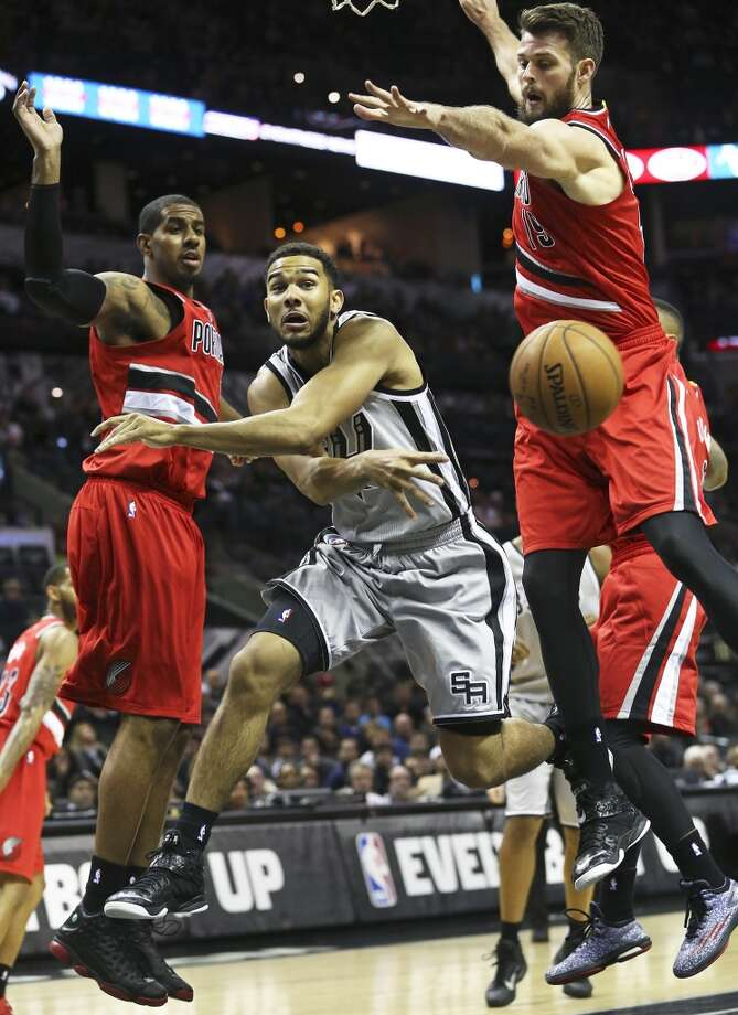 thCorey Joseph draws big men LaMarcus Aldridge and Joel Freeland into the lane and then passes off in the first half as the Spurs host the Portland Trailblazers at the AT&T Center on December 19, 2014.