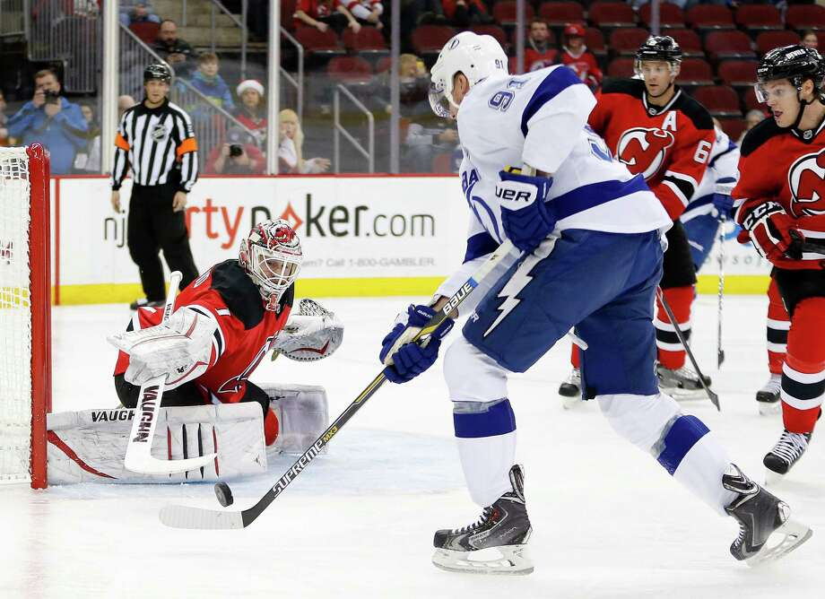 New Jersey Devils goalkeeper Keith Kinkaid, left, defends his net against Tampa Bay Lightning center Steven Stamkos during the first period of an NHL hockey game, Friday, Dec. 19, 2014, in Newark, N.J. (AP Photo/Julio Cortez) ORG XMIT: NJJC105 Photo: Julio Cortez / AP