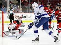 New Jersey Devils goalkeeper Keith Kinkaid, left, defends his net against Tampa Bay Lightning center Steven Stamkos during the first period of an NHL hockey game, Friday, Dec. 19, 2014, in Newark, N.J. (AP Photo/Julio Cortez) ORG XMIT: NJJC105