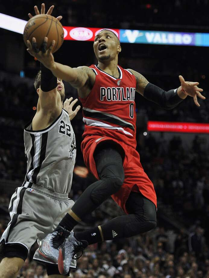 Portland Trail Blazers guard Damian Lillard, right, shoots against San Antonio Spurs forward Tiago Splitter, of Brazil, during the third overtime period of an NBA basketball game, Friday, Dec. 19, 2014, in San Antonio. Portland won 129-119 in triple overtime. (AP Photo/Darren Abate) Photo: Darren Abate, Associated Press