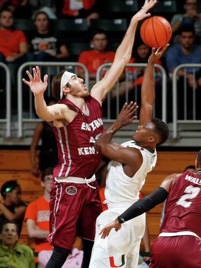 Eastern Kentucky's Eric Stutz (left) blocks a shot attempt by Miami's Deandre Burnett. Photo: Joel Auerbach / Associated Press / FR170673 AP