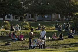 Alberto Sanchez, right, is offered a dollar for a popsicle in Dolores Park in the Mission District of San Francisco, Calif., on Wednesday, October 8, 2014. The paleteros are a staple of the neighborhood who have provided ice cream to generations of Mission residents.