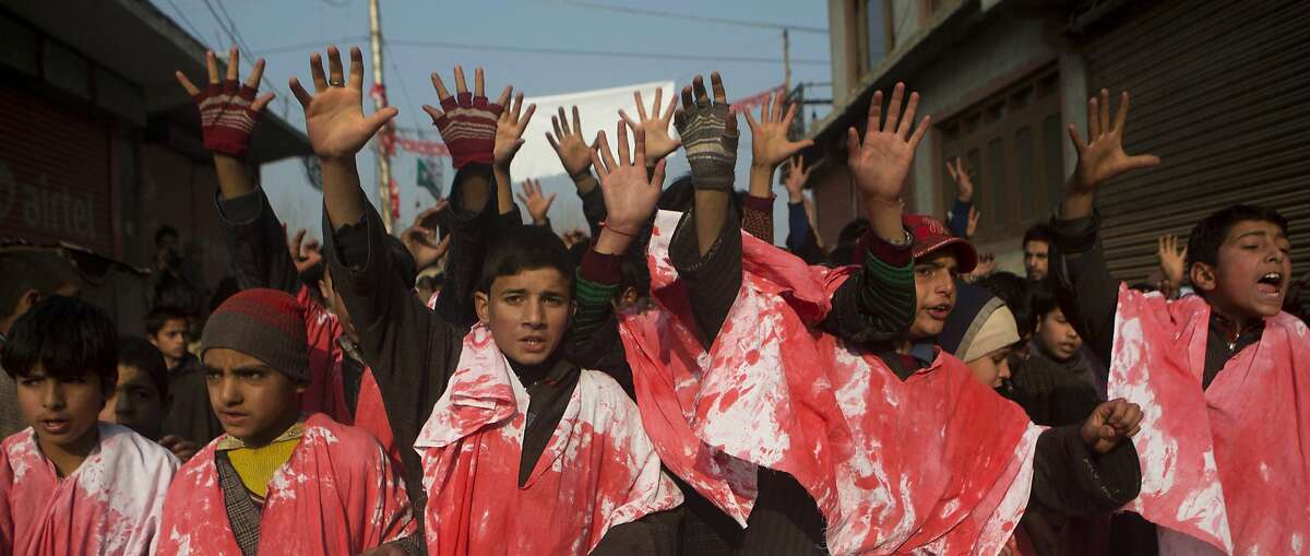 Kashmiri boys wear symbolic burial shrouds and shout slogans during a protest against the Taliban on the outskirts of Srinagar, India, Friday, Dec. 19, 2014. A Taliban massacre killed more than 140 people, mostly children, at a military-run school in northwestern Pakistan. (AP Photo/Dar Yasin)