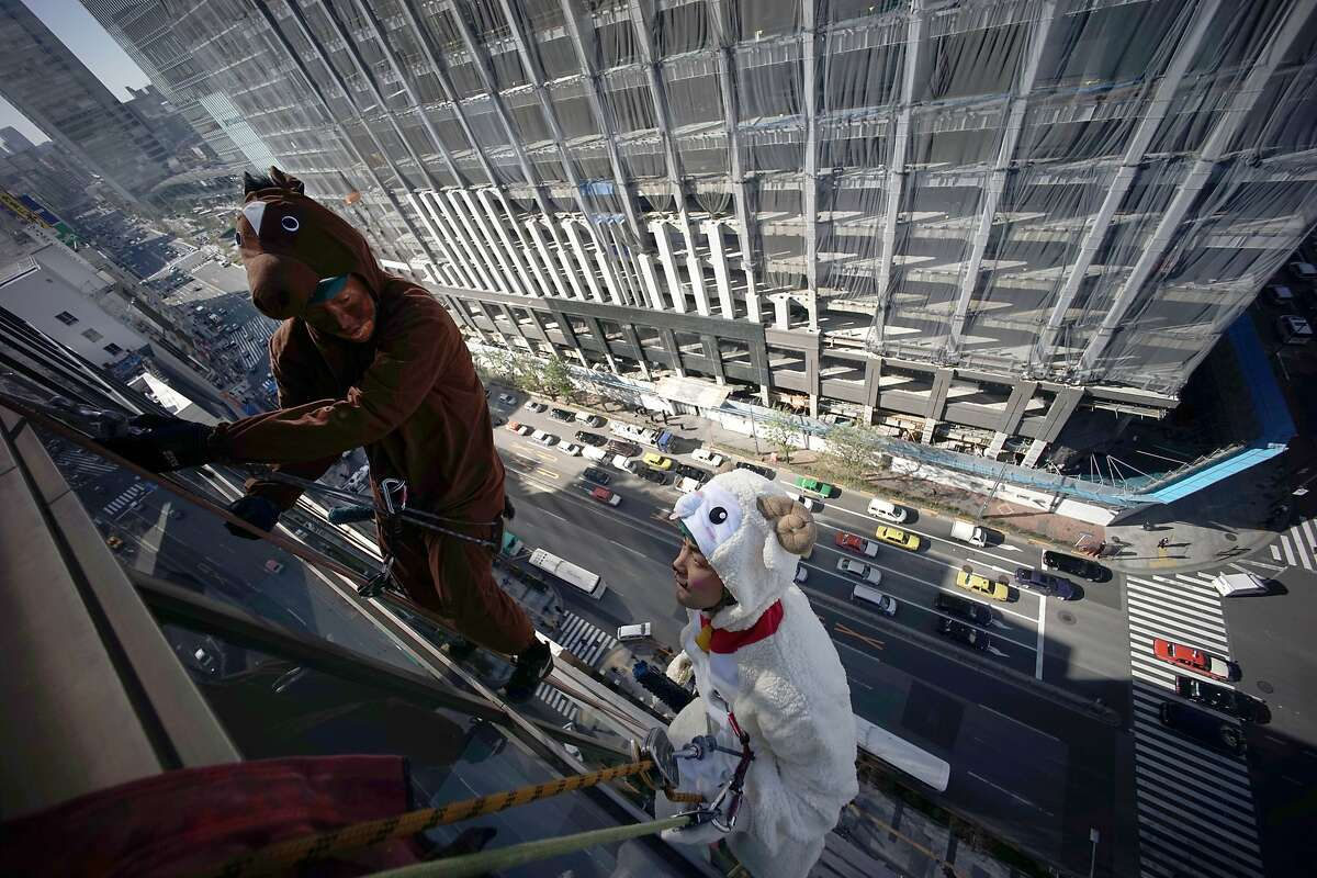 Window cleaners dressed as zodiac animal of horse, and sheep clean the glass exterior of a hotel in Tokyo, Friday, Dec. 19, 2014. During the year end