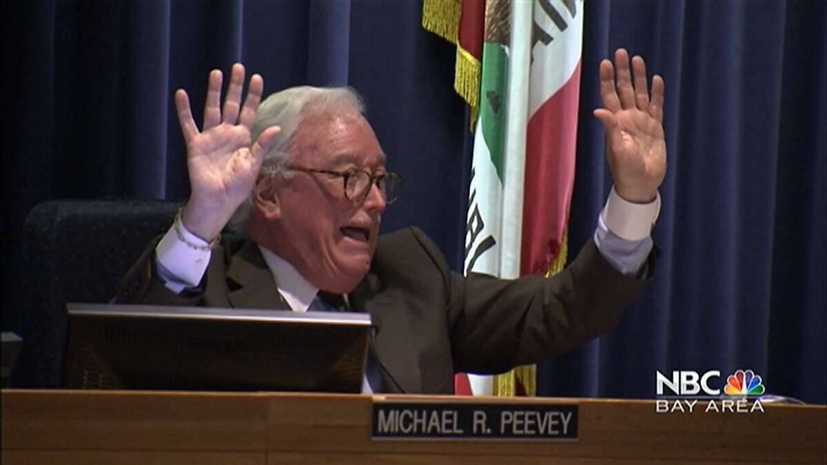 Embattled state Public Utilities Commission President Michael Peevey raises his hands in mock surrender just before giving up his long-held post at his final meeting Thursday.