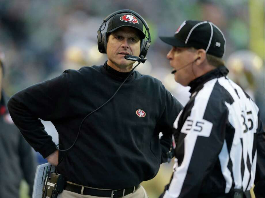 San Francisco 49ers head coach Jim Harbaugh stands near line judge John Hussey during the second half of an NFL football game, Sunday, Dec. 14, 2014, in Seattle. (AP Photo/John Froschauer) Photo: John Froschauer / Associated Press / FR74207 AP