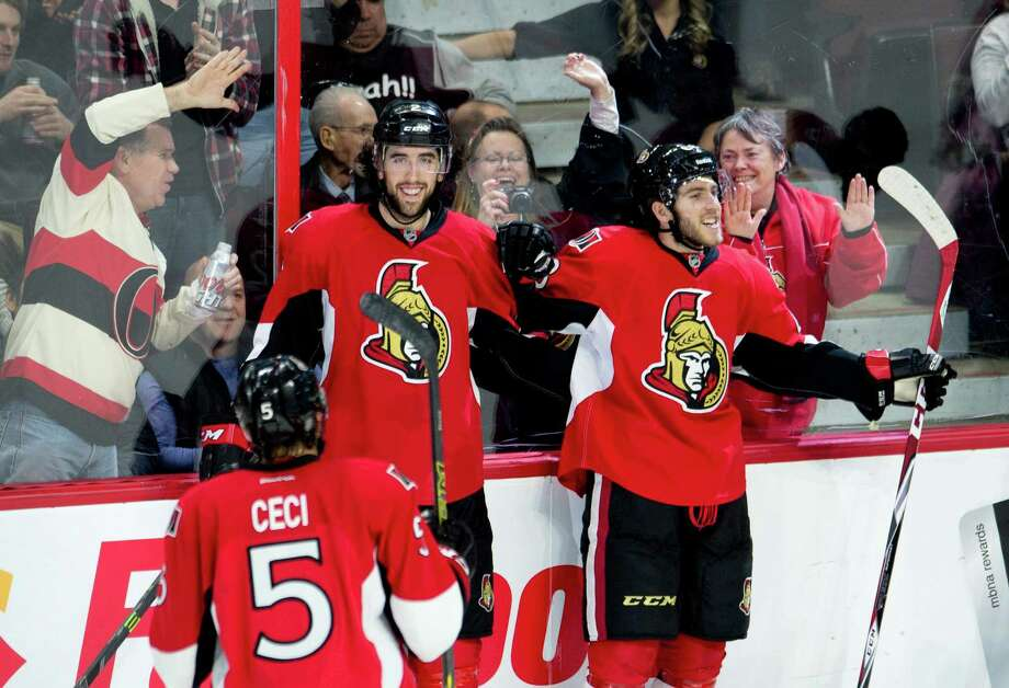 Ottawa Senators left wing Mike Hoffman, right, celebrates his goal with teammates Jared Cowen and Cody Ceci, left, during the second period of an NHL hockey game against the Anaheim Ducks on Friday, Dec. 19, 2014, in Ottawa, Ontario. (AP Photo/The Canadian Press, Adrian Wyld) Photo: Adrian Wyld / Associated Press / The Canadian Press