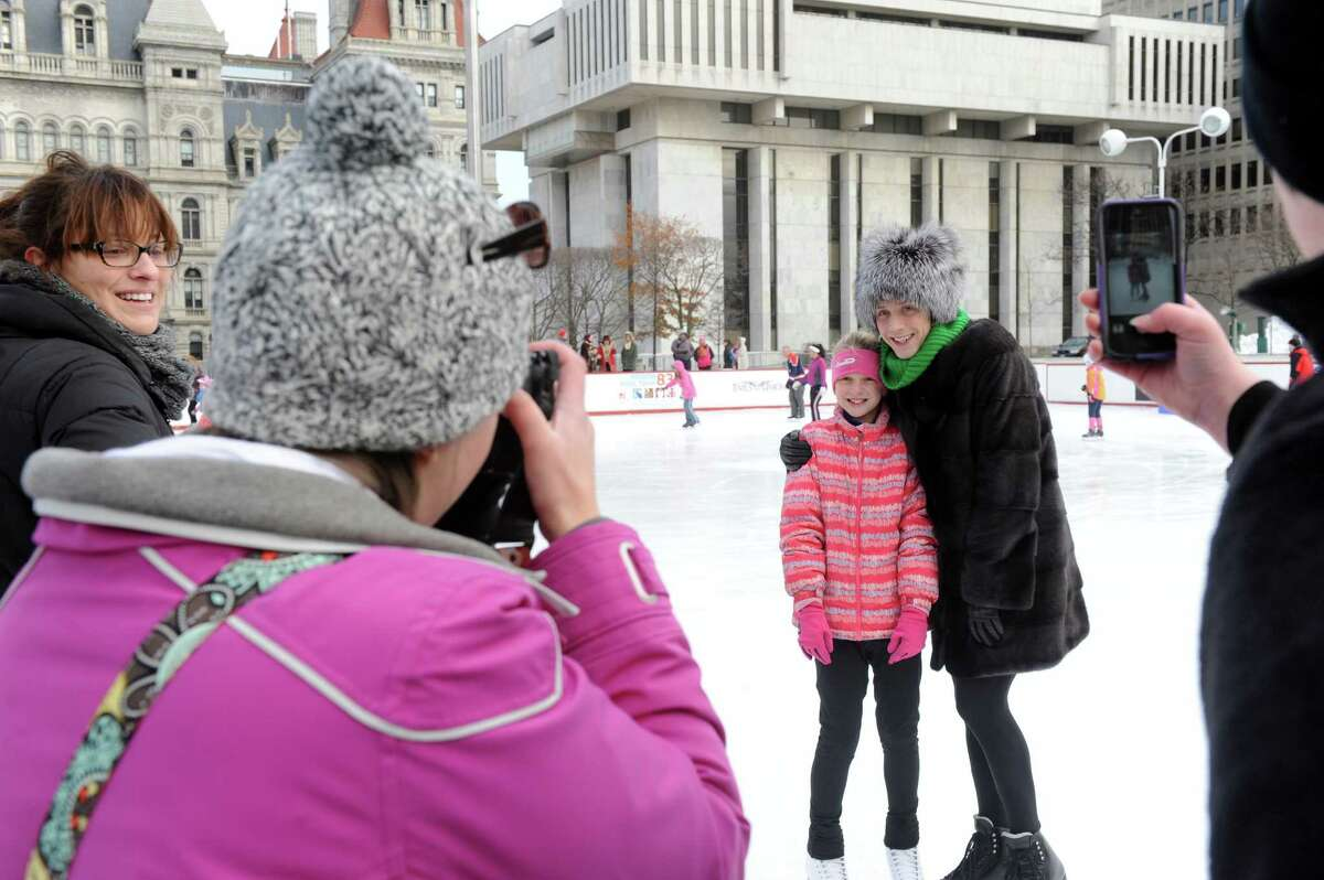 Johnny Weir, a three-time U.S. champion, two-time Olympian, and World medalist in figure skating gets his photograph taken with 10-year-old Cathleen Gossin of Whitesboro during his visit to the Empire State Plaza ice rink on Saturday Dec. 20, 2014 in Albany, N.Y. (Michael P. Farrell/Times Union)