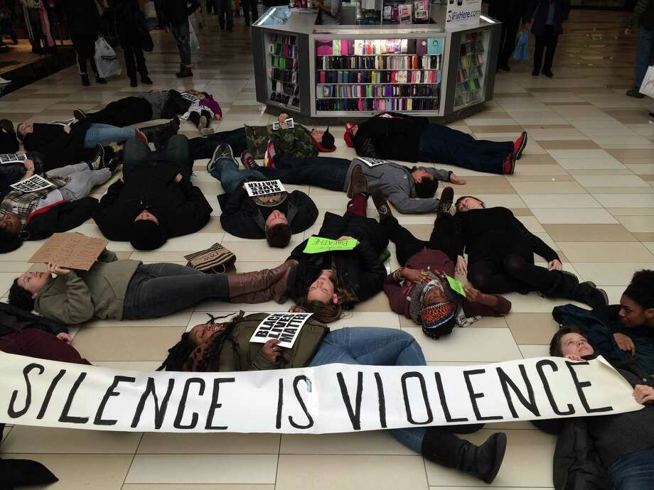 Protesters disrupt the busiest shopping day of the year to remember the life of Eric Garner, an unarmed black man killed by a New York City police officer, at the Crossgates Mall in Albany on Dec. 20, 2014. (Brittany Horn/Times Union) Photo: Brittany Horn/Times Union
