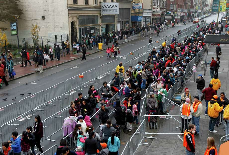 Below, thousands of people line up on Ellis Street for the annual toy giveaway at Glide Memorial Church. Photo: Paul Chinn / The Chronicle / ONLINE_YES