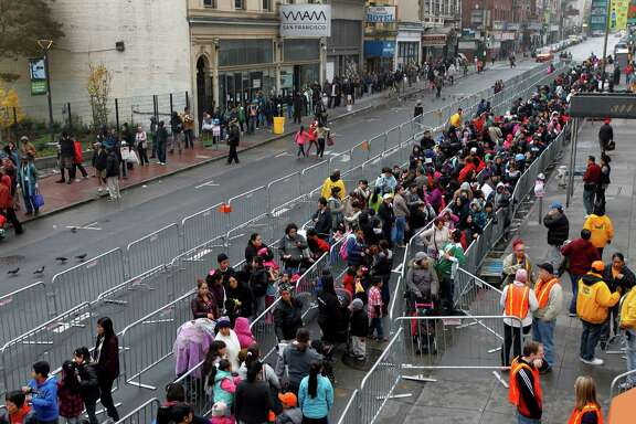 Below, thousands of people line up on Ellis Street for the annual toy giveaway at Glide Memorial Church.