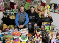 Rob Krieger, of New Fairfield, left, and Andrew Pacewicz, of Fairfield, sit with toys that they have collected and will be distributed by Faith Church, in New Milford. Krieger has been doing the drive for a number of years but missed last year after suffering a stroke. This year he partnered with Faith Church and Sigma chi Alumni of Western Connecticut State University to benefit single moms in the Danbury and New Milford areas.  Saturday, December, 20, 2014, in New Fairfield, Conn.