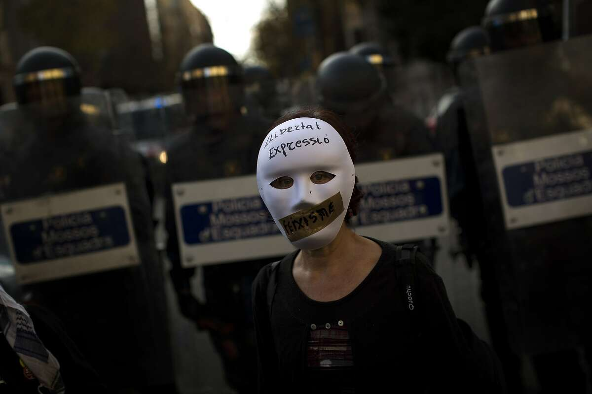 A woman wearing a mask stands in front of riot police officers cordon off the area during a protest against Spanish Citizens Security Law in Barcelona, Spain, Saturday, Dec. 20, 2014. Thousands of people have gathered in several Spanish cities to protest against a new law that sets hefty fines for offenses such as burning the national flag and holding demonstrations outside parliament buildings or strategic installations. The writing on the woman's mask reads in Catalan