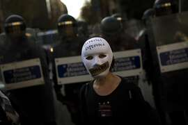 "A woman wearing a mask stands in front of riot police officers cordon off the area during a protest against Spanish Citizens Security Law in Barcelona, Spain, Saturday, Dec. 20, 2014. Thousands of people have gathered in several Spanish cities to protest against a new law that sets hefty fines for offenses such as burning the national flag and holding demonstrations outside parliament buildings or strategic installations. The writing on the woman's mask reads in Catalan ""freedom of expression"". (AP Photo/Emilio Morenatti)"