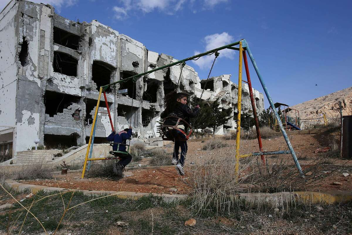 TOPSHOTS Children play on a swing in the park of the Safir Maalula Hotel, in the ancient Christian town of Maalula, 56 kilometers northeast of the Syrian capital Damascus, on December 20, 2014. AFP PHOTO / YOUSSEF KARWASHANYOUSSEF KARWASHAN/AFP/Getty Images