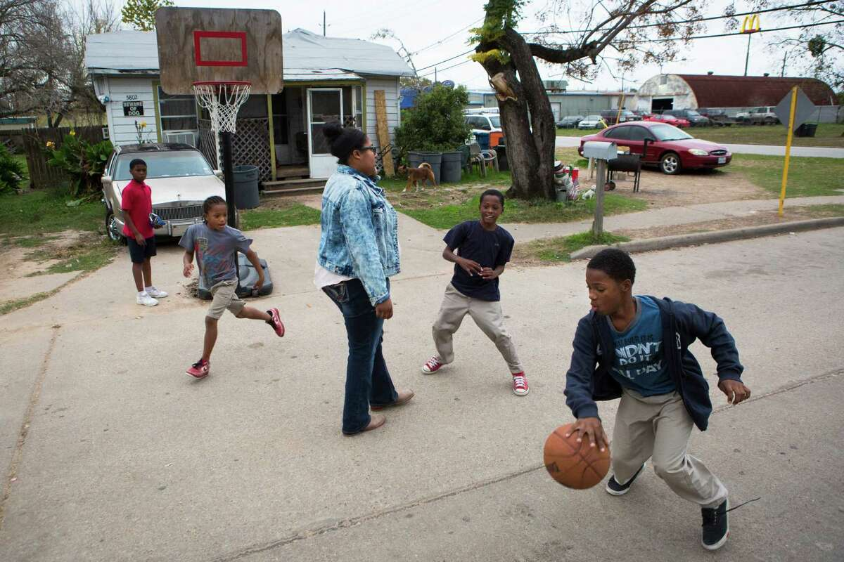 From right, Tremel Cooper, 11; Bryan Worthy, 9; Katelyn Washington, 16; and Byron Worthy, 9, play street basketball near their homes on the corner of Roberts and Danover  in Katy.