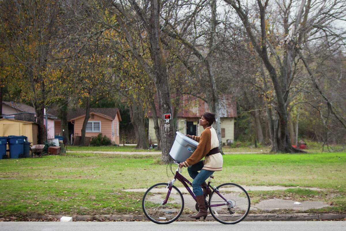 A woman rides a bicycle down Danover Street in Katy on Wednesday. Katy has gained a reputation for being unwelcoming to developers of low-income housing.