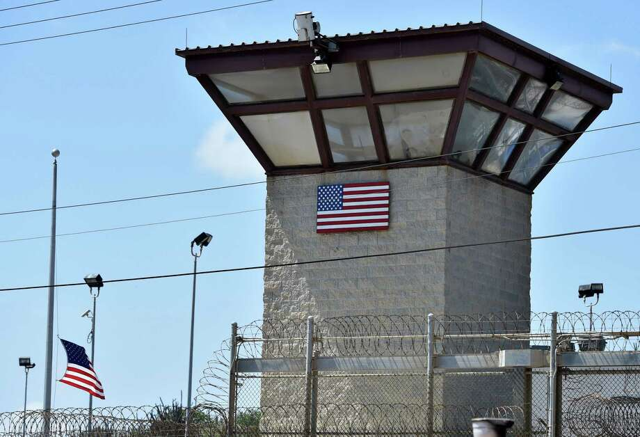 "(FILES)This April 8, 2014 file photo made during an escorted visit and reviewed by the US military shows the razor wire-topped fence and the watch tower of ""Camp 6"" detention facility at the US Naval Station in Guantanamo Bay, Cuba.  Four detainees held at the Guantanamo Bay US military prison have been repatriated to Afghanistan, the Pentagon said December 20, 2014. The Department of Defense said that the Afghan men -- Shawali Khan, Khi Ali Gul, Abdul Ghani, and Mohammed Zahir -- had been moved from the prison after a comprehensive review of their case. ""As a result of that review, which examined a number of factors, including security issues, these men were unanimously approved for transfer by the six departments and agencies comprising the task force,"" a Pentagon statement said. The releases come hard on the heels of the transfer of six Guantanamo detainees to start new lives in Uruguay earlier this month. AFP PHOTO/MLADEN ANTONOVMLADEN ANTONOV/AFP/Getty Images Photo: MLADEN ANTONOV / AFP"