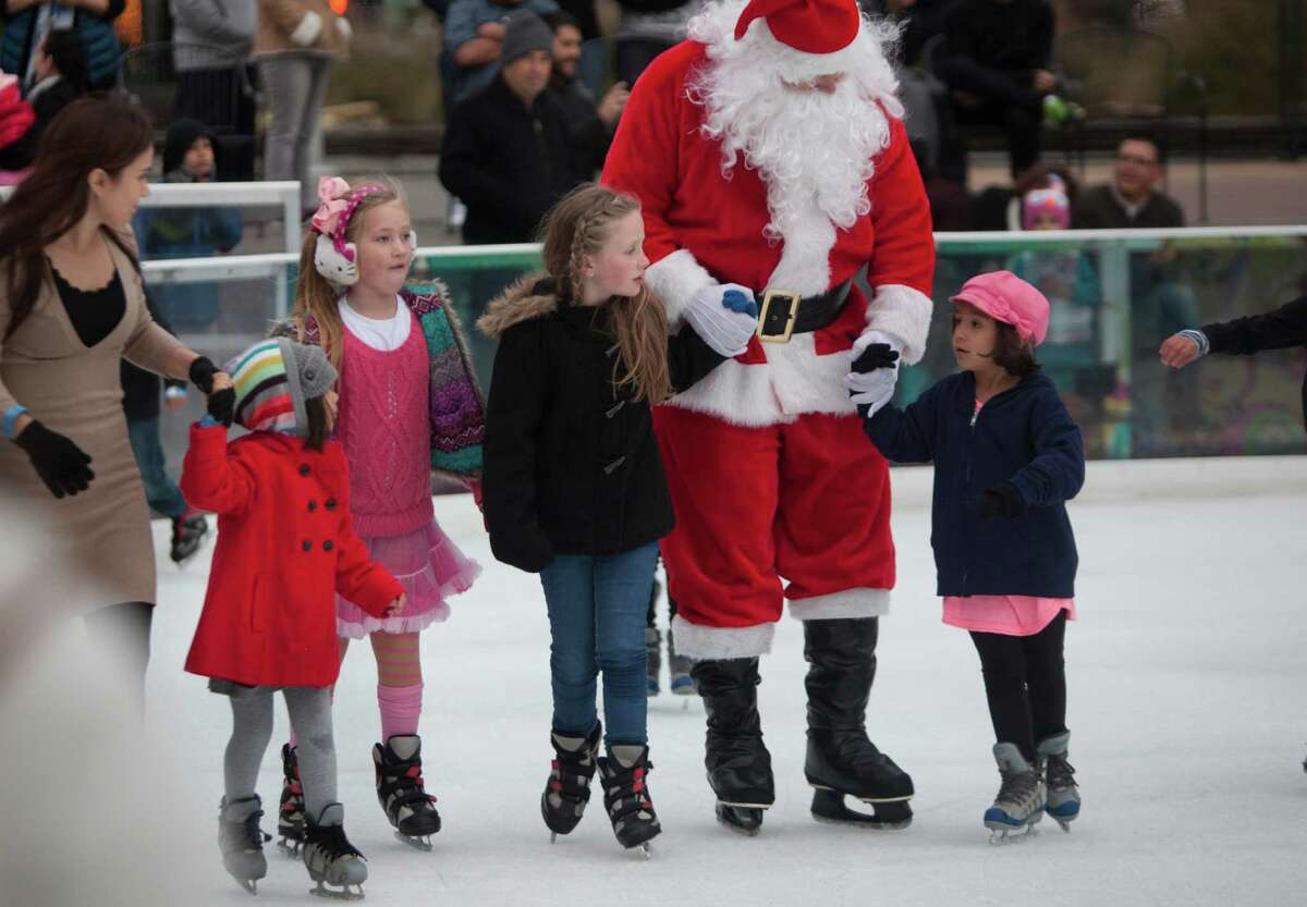 Santa Claus skates with (left to right) Diana Rios, Sofia Rios, 4, Franchesca Lefler, 8, Paisley Lefler, 8, and Madison Rabassa at Discovery Green Ice, Saturday, Dec. 20, 2014, in Houston.