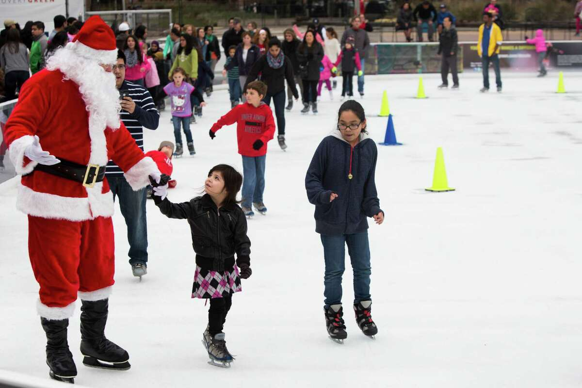 Madison Alba, 4, of Houston stares at Santa Claus while she skates with him at Discovery Green Ice, Saturday, Dec. 20, 2014, in Houston.