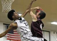Bethel's Will Daniels (4) goes up for a shot and is fouled by Immaculate's Jade Martin (20) during the News Times Greater Danbury Tip Off Classic boys varsity basketball championship game between the Bethel Wildcats and the Immaculate Mustangs, on Saturday night, December 20, 2014, played at theDanbury War Memorial, in Danbury, Conn.