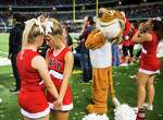 Katy cheerleaders join hands with the game tied in the final minute of a loss to Cedar Hill in the Class 6A Division II state football title game at AT&T Stadium Saturday, Dec. 20, 2014, in Arlington.