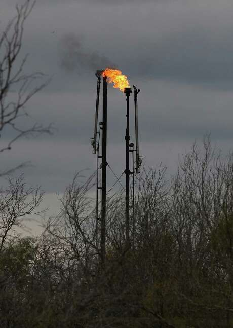 A flare burns natural gas at the Brown Trust oil lease near Cotulla on Highway 97 in La Salle County on Thursday, Dec. 11, 2014. Operated by Carrizo (Eagle Ford) LLC, flares at the lease burned more than 250 million cubic feet of gas in the first seven months of 2014, nearly a third of overall production according to data obtained from the Texas Railroad Commission. (Kin Man Hui/San Antonio Express-News) Photo: Kin Man Hui, Staff / San Antonio Express-News / ©2014 San Antonio Express-News