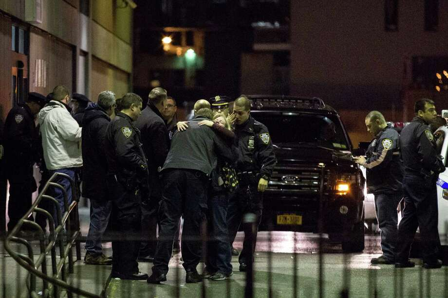 """The emotional scene outside the emergency room of Woodhull Hospital in Brooklyn where two New York police officers died after being shot, Saturday, Dec. 20, 2014.  The two officers were fatally shot in their patrol car in Brooklyn on Saturday in what the mayor and the police commissioner called an """"assassination"""" by a suspect who later killed himself with a gunshot to the head. (Kevin Hagen/The New York Times) Photo: Kevin Hagen / New York Times / NYTNS"""