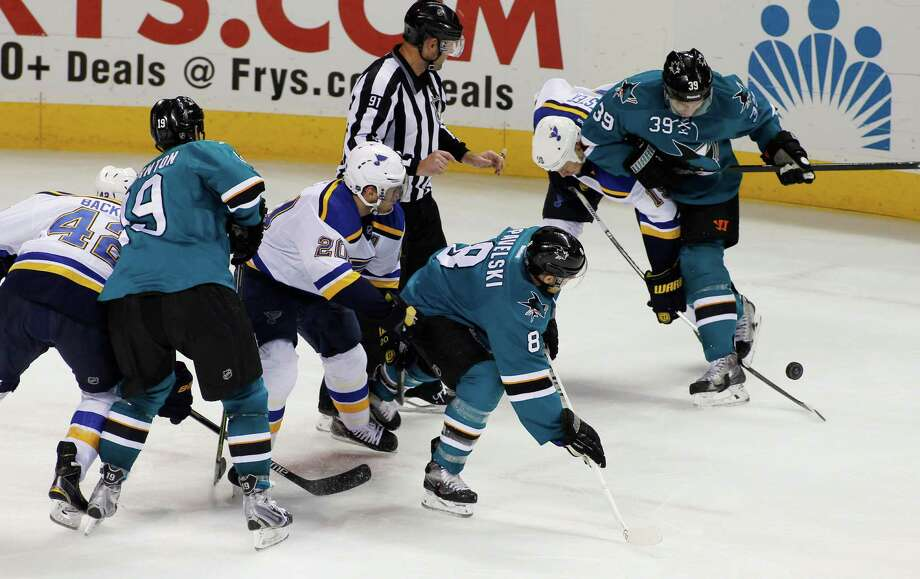 Jay Bouwmeester (second from right) and the Sharks' Logan Couture fight for the puck. Photo: George Nikitin / Associated Press / FR57659 AP