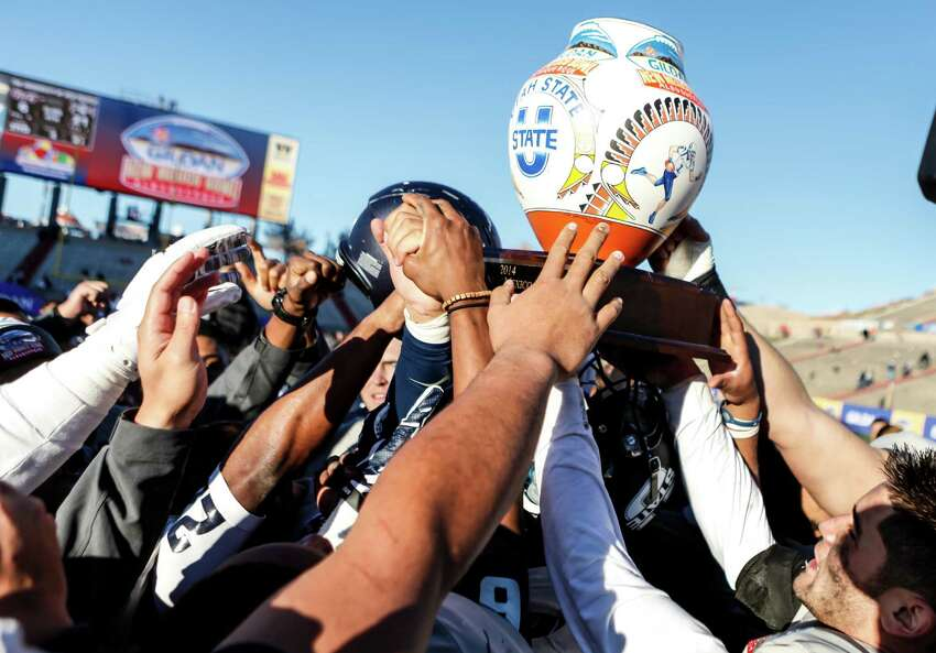 Gildan New Mexico Bowl Utah State 21, UTEP 6 AudioSource Sound portable/mobile speakers, mobile phone chargers, Oakley Works backpacks, Oakley Enduro sunglasses/beanies, caps, and Gildan blankets. The Utah State Aggies hold up the Gildan New Mexico Bowl Trophy after defeating the UTEP Miners on Dec. 20, 2014.