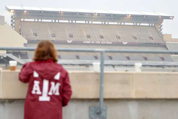 Texas A&M alumnus Niky Jackson stands atop the west side parking garage on the Texas A&M University campus in College Station, Texas, looking toward the east side of Kyle Field after the west side was imploded Sunday, Dec. 21, 2014. The section was imploded to make way for a new facade and facilities as part of a $450 million renovation. (AP Photo/College Station Eagle, Sam Craft)