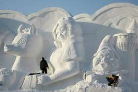 HARBIN, CHINA - DECEMBER 20:  (CHINA OUT) Workers put the finishing touch to a sculpture prior to the 27th Harbin Sun Island International Snow Sculpture Art Expo on December 20, 2014 in Harbin, China. The expo will be open to the public today.
