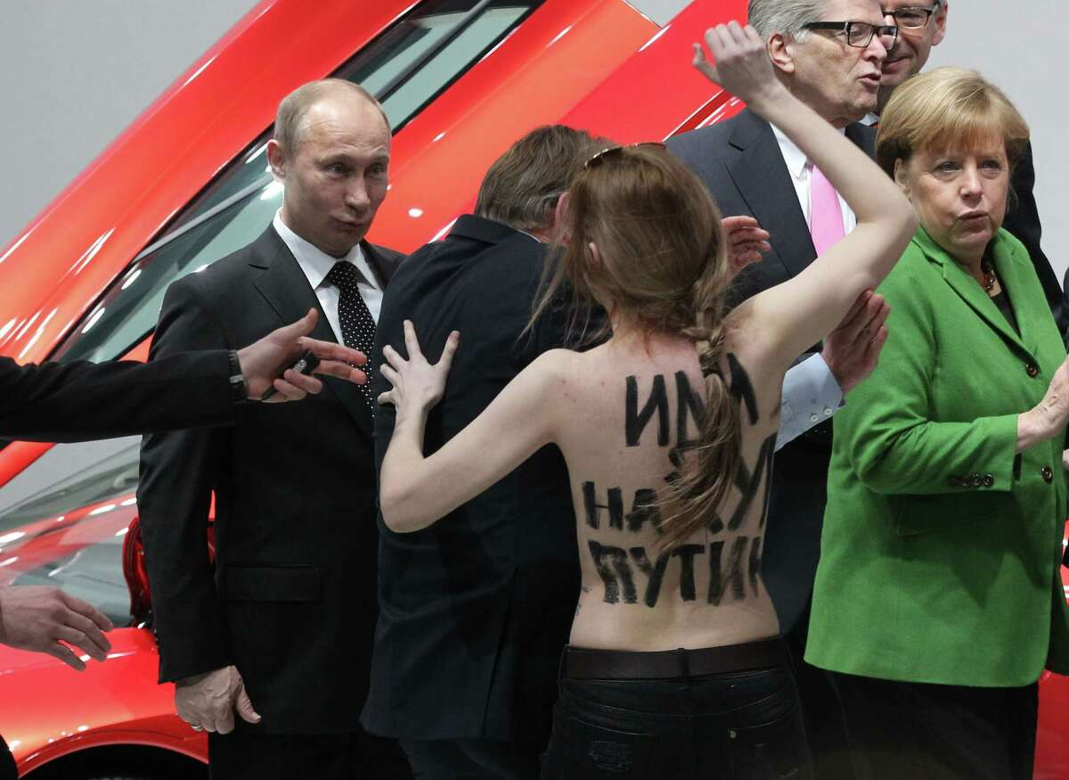 Russian President Vladimir Putin (L) is attacked by an activist of the Ukrainian women rights group 'Femen' as German Chancellor Angela Merkel (R) looks on during their visit of the industrial exhibition 'Hannover Messe' on April 8, 2013 in Hannover, Germany.