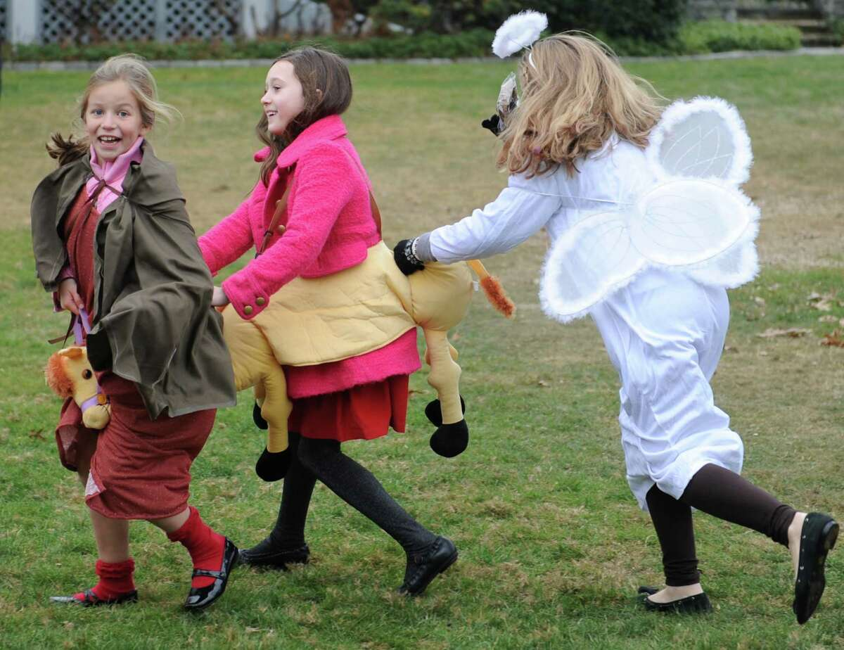 Sisters Lara Olmsted, left, 8, and Jennie Olmsted, right, 11, of Riverside, try to hop on the camel of Tessa Laffan, 9, of Greenwich, during a live nativity at First Congregational Church in Old Greenwich, Conn. Sunday, Dec. 21, 2014. Church members dressed as Mary, Joseph, kings and shepherds, complete with live sheep as they sang Christmas carols before a small audience outside the church.