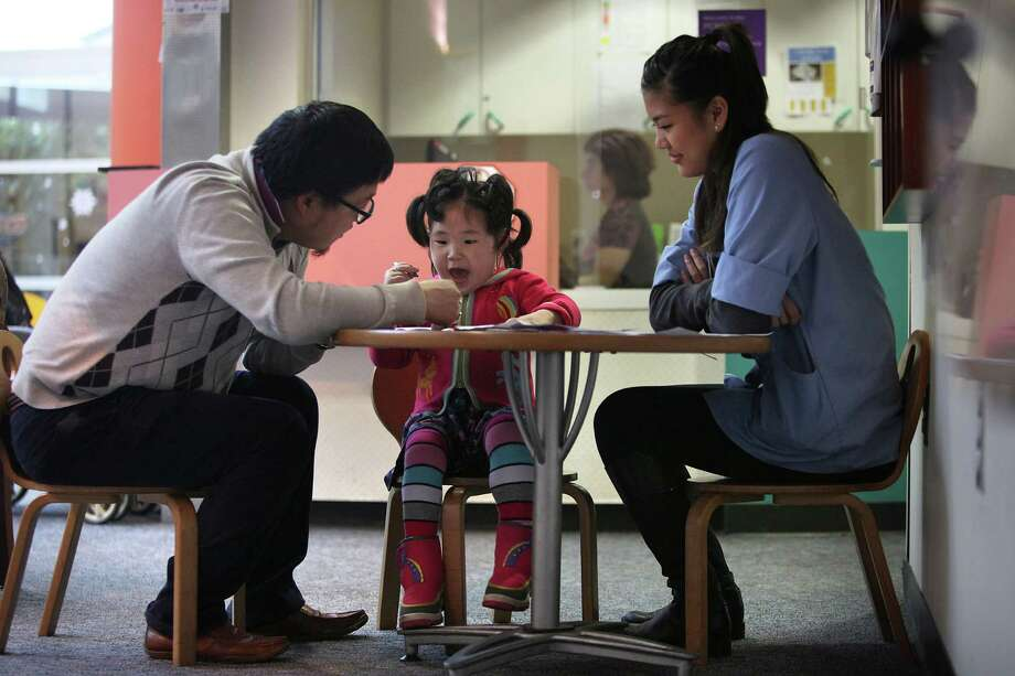 Nomin Gan-Erdene, 4, sits with her father, Gan-Erdene Ganbat (left) and volunteer Shannel Vidallon at UCSF Benioff Children's Hospital Oakland, as they wait for an appointment Dec. 15. Children's Hospital Oakland is one of a few facilities in the world participating in a clinical trial for neurodegeneration with brain iron accumulation. Photo: Liz Hafalia / The Chronicle / ONLINE_YES