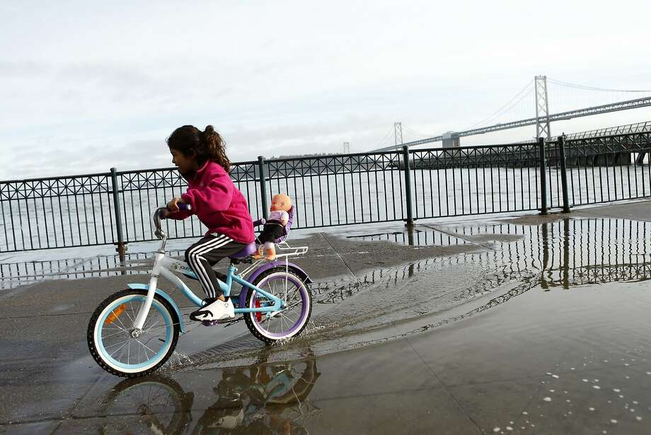 Priscilla Ferreira, 8, rides her bicycle as water from the high tide starts to flow onto the pavement near Pier 14 in San Francisco, Calif., on Sunday, December 21, 2014. Photo: Scott Strazzante, The Chronicle