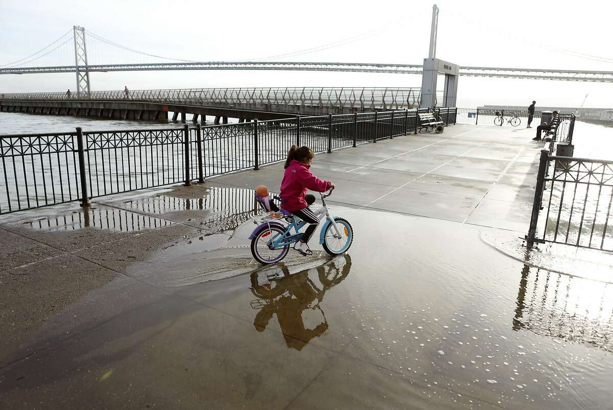 Priscilla Ferreira, 8, rides her bicycle as water from the high tide starts to flow onto the pavement near Pier 14 in San Francisco, Calif., on Sunday, December 21, 2014.